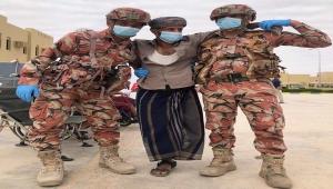 جنديان عمانيان يحملان جريحا يمنيا.. صورة تصدرت المنصات باليمن