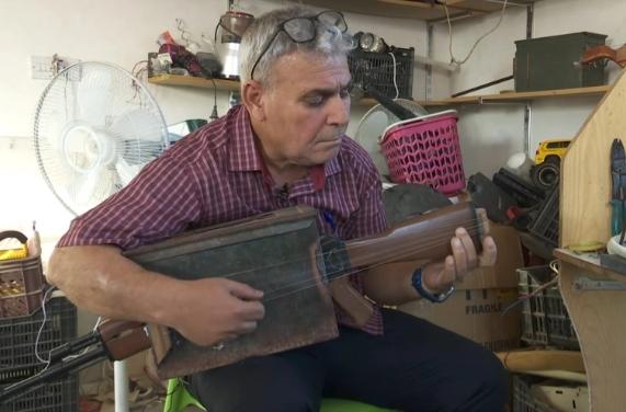 """عزف بـ """"الكلاشنكوف"""".. مدرس عراقي يحول بندقية إلى آلة موسيقية فريدة (فيديو)"""